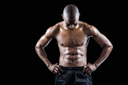 masculinity: Muscular man with hand on hip looking down while standing against black background