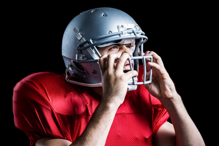 cut the competition: Aggressive American football player holding helmet while playing against black background Stock Photo