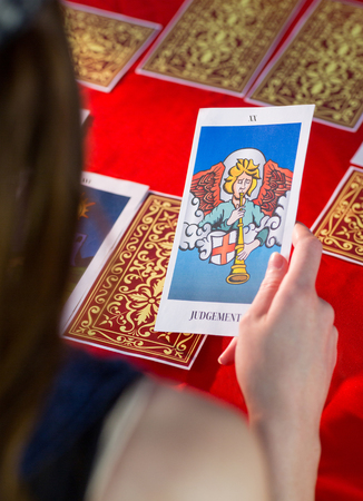 telepathy cards: Fortune teller using tarot cards on red table Editorial
