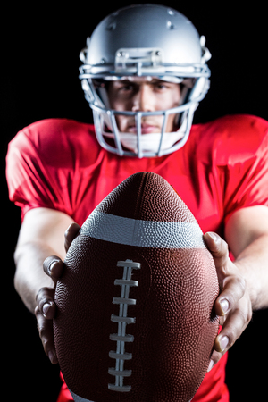 cut the competition: Portrait of sportsman showing American football against black background Stock Photo