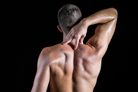 back sprains: Rear view of shirtless athlete with neck pain over black background Stock Photo