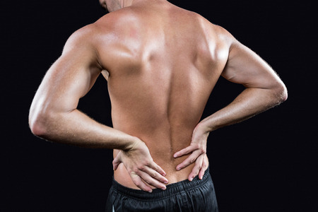 shirtless: Vista trasera del hombre sin camisa con dolor de espalda contra el fondo negro Foto de archivo