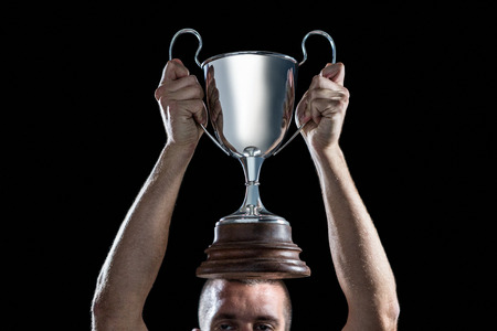 high section: High section of successful rugby player holding trophy against black background