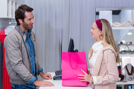 clothing store: Smiling woman talking to cashier in clothing store Stock Photo