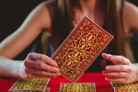 Wahrsagerin mit Tarot-Karten auf schwarzem Hintergrund Lizenzfreie Bilder
