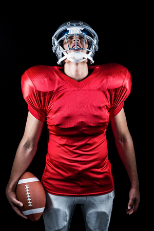 padding: American football player holding ball while looking up against black background Stock Photo