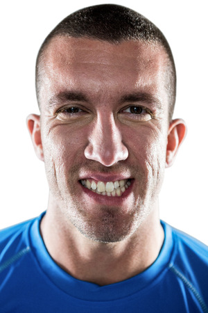 clenching teeth: Portrait of rugby player clenching teeth against white background