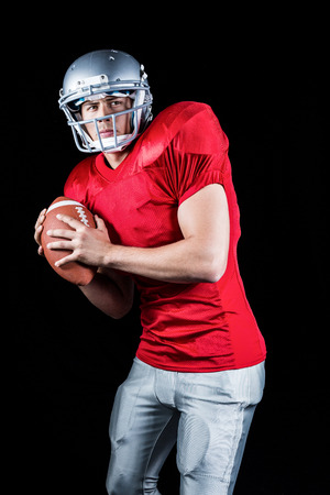 padding: Determined American football player holding ball against black background Stock Photo
