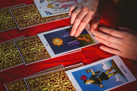 Fortune teller using tarot cards on red table Editorial