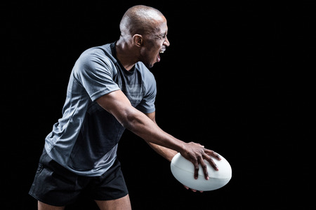 sportsman: Sportsman playing rugby over black background