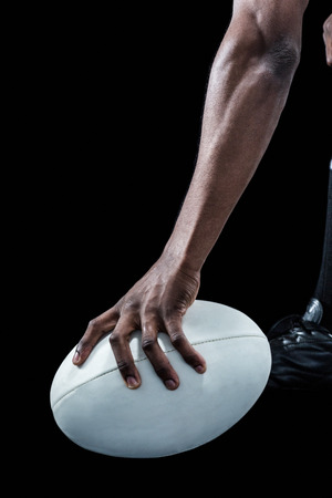 cropped: Cropped image of athlete holding rugby ball over black background Stock Photo