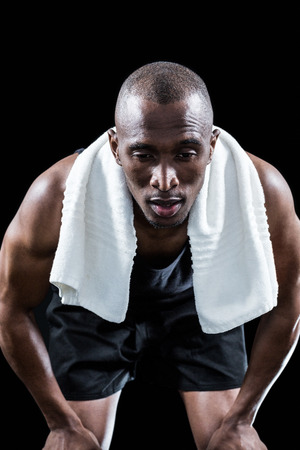 knee bend: Muscular man with towel around neck resting while keeping hand on knee on black background