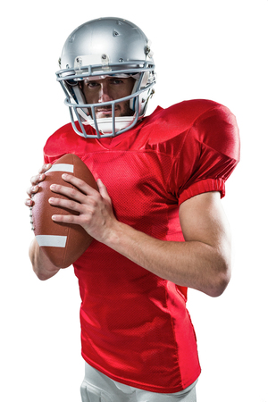 cut the competition: Portrait of confident sports player in red jersey holding ball on white background Stock Photo