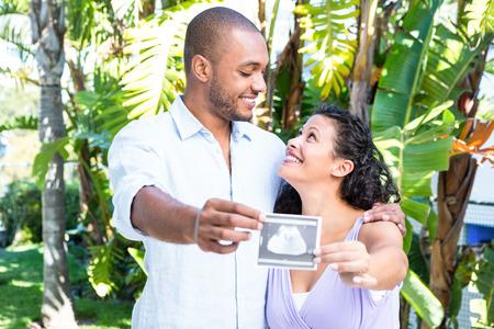 sonograma: Marido feliz con la mujer embarazada que sostiene sonograma contra el fondo blanco Foto de archivo