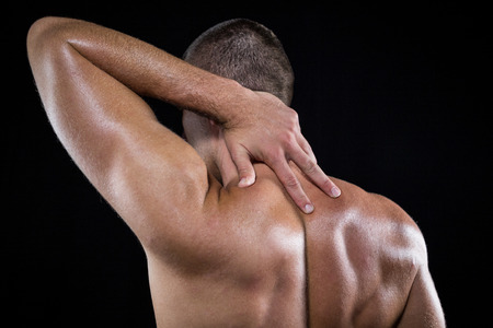 back sprains: Rear view of shirtless man with neck pain over black background