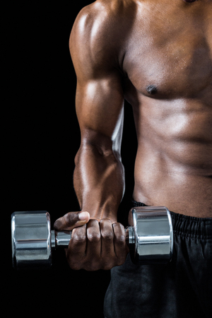 athletic body: Cropped image of muscular man exercising with dumbbell against black background
