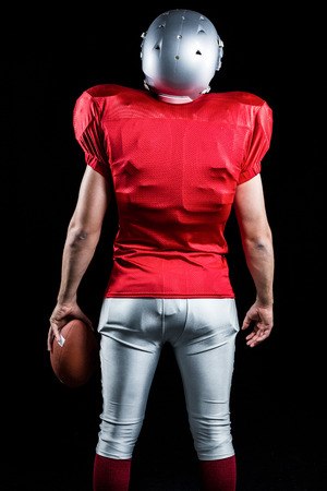 cut the competition: Rear view of American football player with ball standing against black background