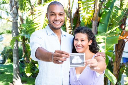 sonogram: Retrato de hombre feliz con esposa embarazada sosteniendo sonograma contra el fondo blanco