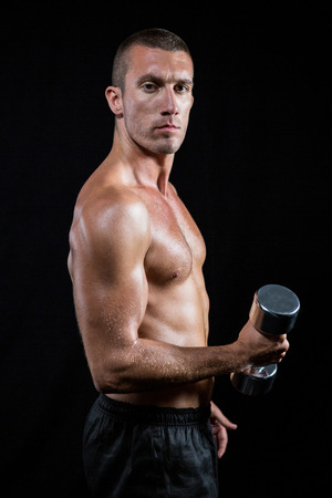 free weight: Portrait of confident shirtless athlete working out with dumbbell against black background Stock Photo