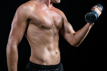 free weight: Midsection of shirtless athlete working out with dumbbell against black background