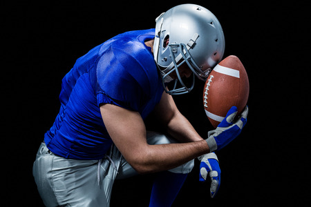 blue helmet: Upset American football player with ball against black background Stock Photo