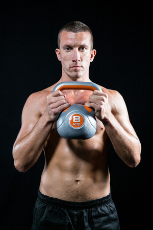 free weight: Portrait of confident shirtless athlete working out with kettlebell against black background