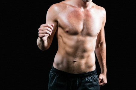 athleticism: Midsection of shirtless athlete running against black background