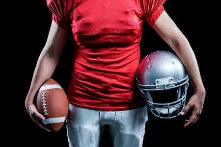 padding: Mid section of sportsman holding American football and helmet against black background