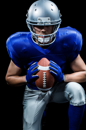 padding: Determined American football player holding ball while kneeling against black background