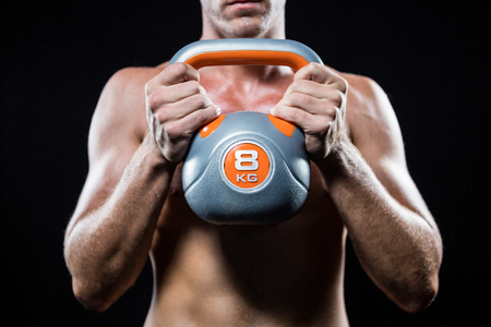 free weight: Midsection of shirtless athlete holding kettlebell against black background