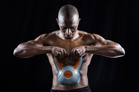 man looking down: Muscular man looking down while exercising with kettlebell against black background