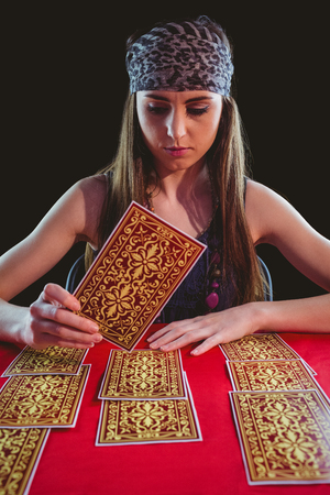 telepathy: Fortune teller using tarot cards on black background
