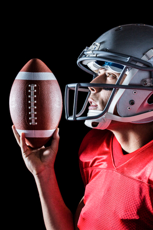 looking up: Sportsman looking up while holding American football against black background