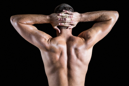 standing against: Rear view of shirtless muscular man standing against black background Stock Photo