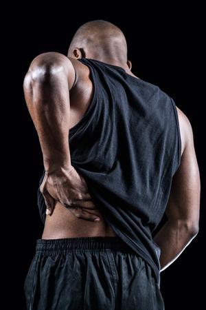 dolor espalda: Vista trasera del atleta musculoso sufrimiento a través de dolor de espalda contra el fondo negro