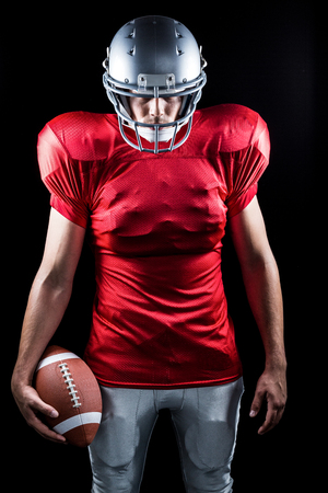 cut the competition: American football player standing with ball against black background