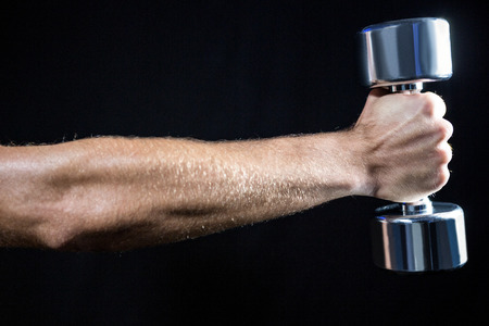 cropped out: Cropped image of man working out with dumbbell against black background