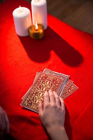 teller: Fortune teller using tarot cards on red table Stock Photo