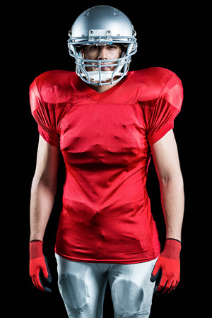 cut the competition: Portrait of American football player standing over black background