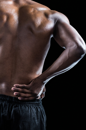 back pain: Cropped image of muscular athlete suffering through back pain against black background Stock Photo