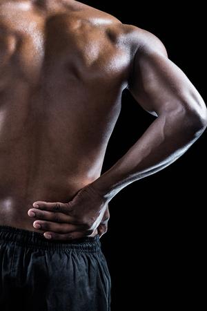 dolor espalda: Imagen recortada de atleta musculoso sufrimiento a través de dolor de espalda contra el fondo negro