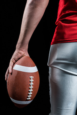 cut the competition: Cropped image of American football player holding ball against black background