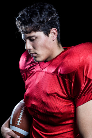 padding: American football player holding ball while eyes closed against black background
