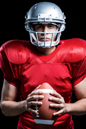 cut the competition: Portrait of serious American football player holding ball against black background Stock Photo