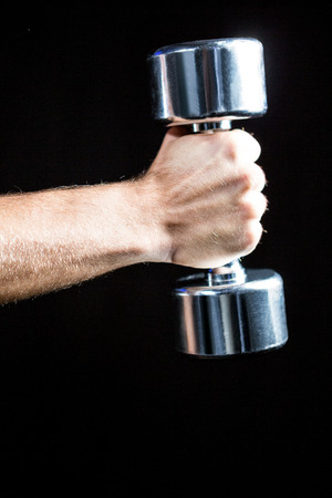 free weight: Close-up of of man working out with dumbbell against black background