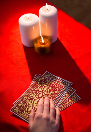 telepathy cards: Fortune teller using tarot cards on red table Stock Photo