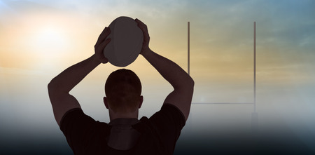 rugby: Rugby player about to throw a rugby ball against goals posts Stock Photo