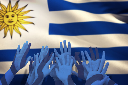 raise the white flag: People raising hands in the air against close-up of uruguayan flag Stock Photo