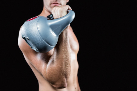 free weight: Midsection of shirtless man working out with kettlebell against black background Stock Photo