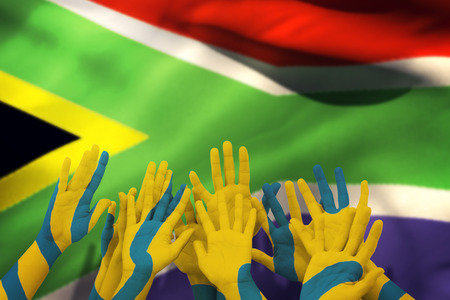 raise the white flag: People raising hands in the air against flag of south africa Stock Photo